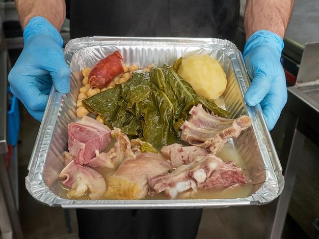 De handen van een chef-kok die een folie houden halen container met een traditionele spaanse stoofpot weg