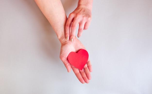 De handen van een dame die een hart boven het oppervlak houdt,