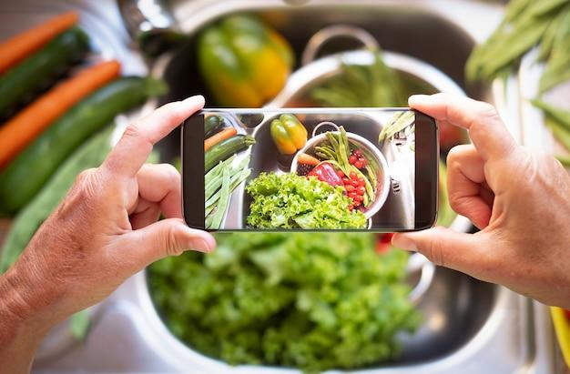 De handen van een dame nemen een foto met mobiele telefoon naar de schoongemaakte groenten in de gootsteen