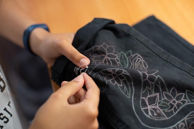 De handen van een jong meisje borduren een zwarte broek, handwerk