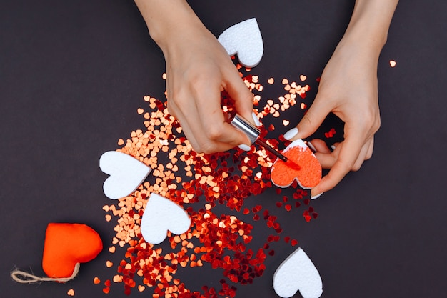 De handen van een jong meisje verven het hart rood. in de cirkel van vele kleine hartjes, valentijnsdag
