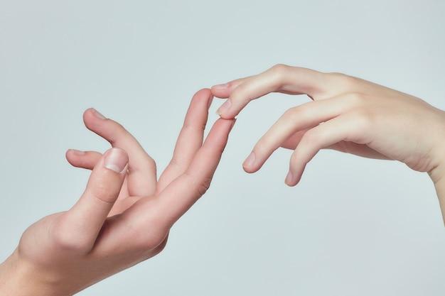 De handen van een jonge jongen en een jong meisje reiken naar elkaar. witte achtergrond