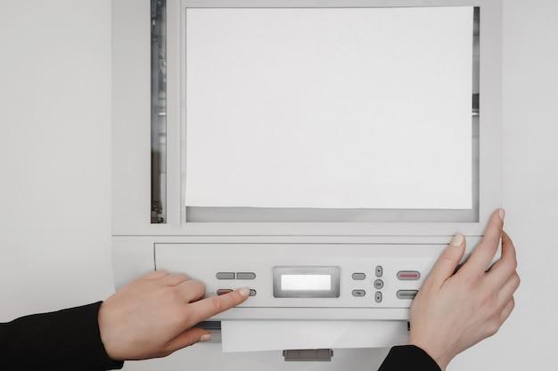 De handen van een jonge vrouw die een stuk papier op een flatbedscanner legt