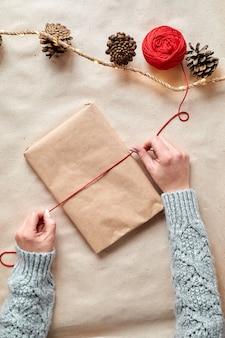 De handen van een jonge vrouw maken kerstcadeautjes en verpakken ze