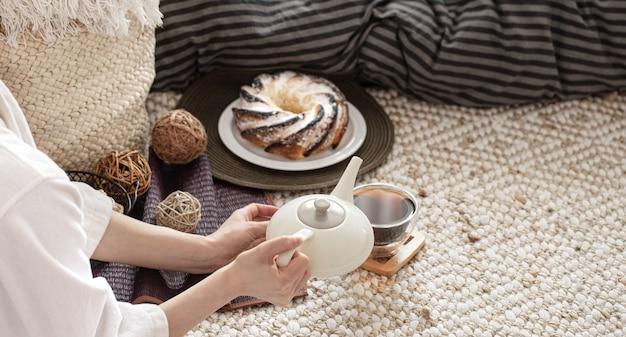 De handen van een jonge vrouw schenken thee uit een theepot. ontbijt klaarmaken in een gezellige huiselijke sfeer.