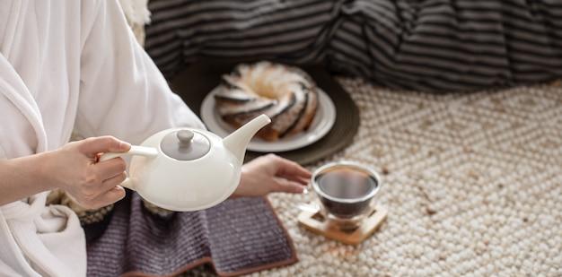 De handen van een jonge vrouw schenken thee uit een theepot.