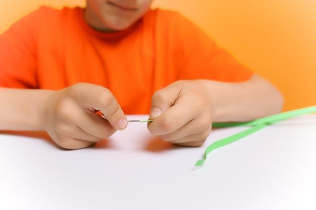 De handen van een jongen in close-up die dunne papieren stroken in een draaigereedschap in de quilling-techniek steekt