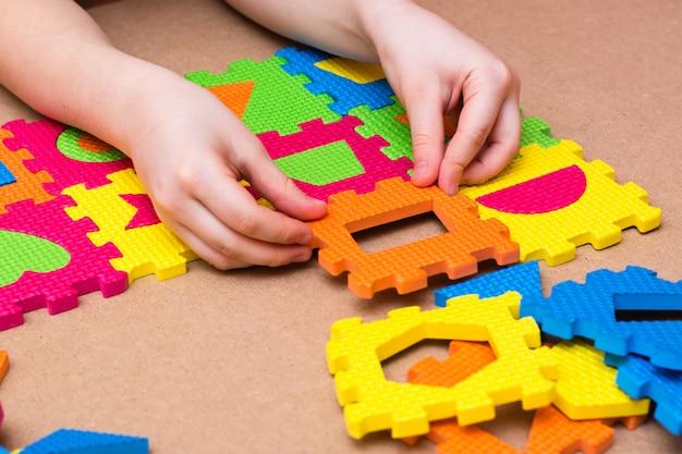 De handen van een kind stellen een kleurenpuzzel samen met details van verschillende geometrische vormen op tafel. vrije tijd van het kind in opsluiting