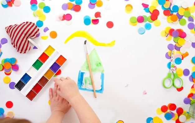 De handen van een kind tekenen met aquarellen op een witte achtergrond bovenop. kleurrijke confetti. detailopname