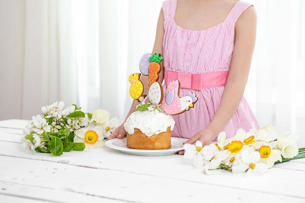 De handen van een klein meisje dat een feestelijke taart versiert. het concept van de voorbereiding op de paasvakantie.