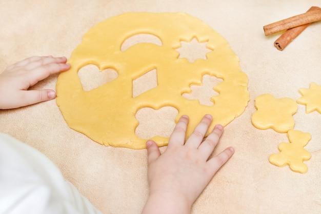 De handen van een klein meisje maken een gebakjekoekje. kerst bakken