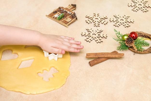De handen van een klein meisjesachtig meisje maken een gebakjekoekje. kerst bakken