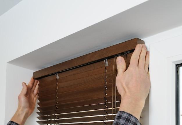 De handen van een man bevestigen een decoratieve staaf bovenop houten jaloezieën