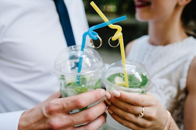 De handen van een man en een vrouw houden plastic glazen wijn of champagne en twee trouwringen vast