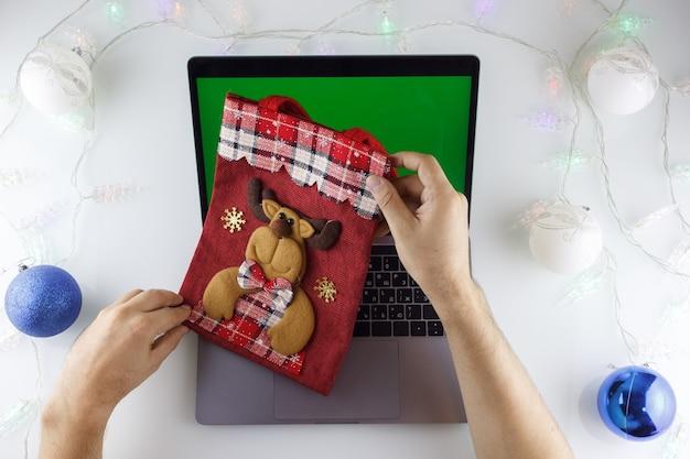 De handen van een man houden een rode kerstzak vast over een laptop met een groen scherm