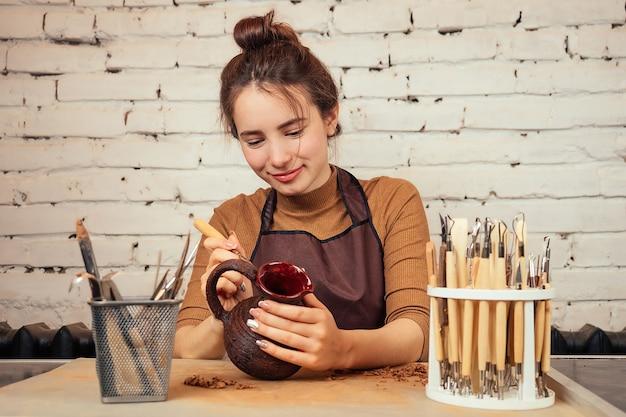 De handen van een man in klei op een pottenbakkersschijf vormen een vaas. de pottenbakker werkt in een pottenbakkerij met klei. het concept van aardewerk meesterschap en creativiteit
