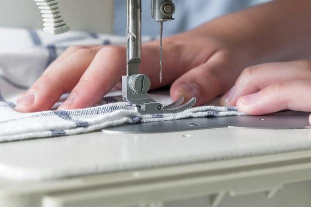 De handen van een meisje naait op een wit naaimachineclose-up op een blauwe achtergrond met exemplaar ruimte selectieve nadruk