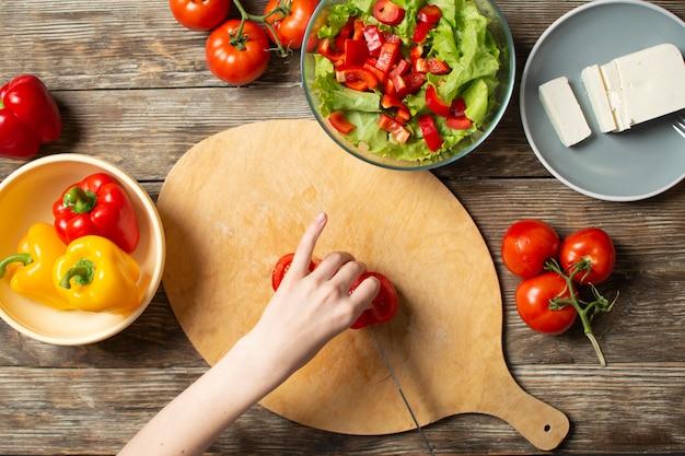 De handen van een meisje snijden tomates op een houten lijst