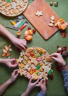 De handen van een mooie jonge vrouw die een gebakken gemberman vasthoudt. het concept van een feest in huis, een familiediner. nieuwjaar tradities concept en kookproces. familie maken