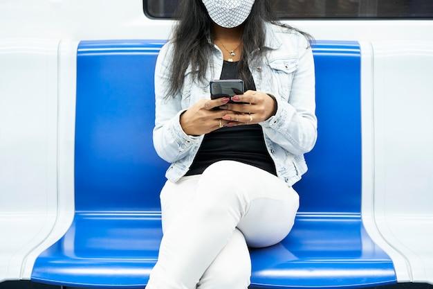 De handen van een onherkenbare zwarte vrouw die met een smartphone in de metro zit