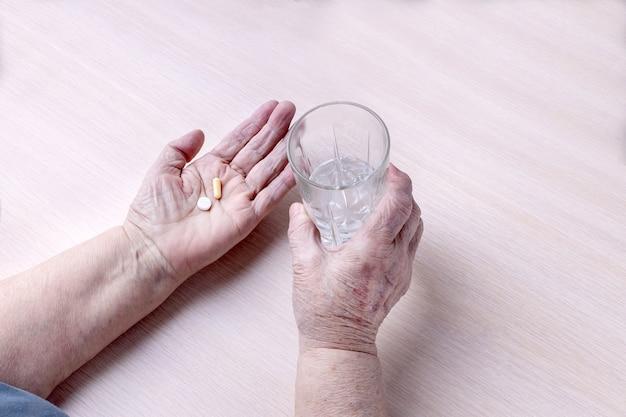 De handen van een oude vrouw met een glas water en pillen