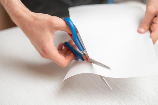 De handen van een persoon houden een stuk papier vast en knippen het met een schaar