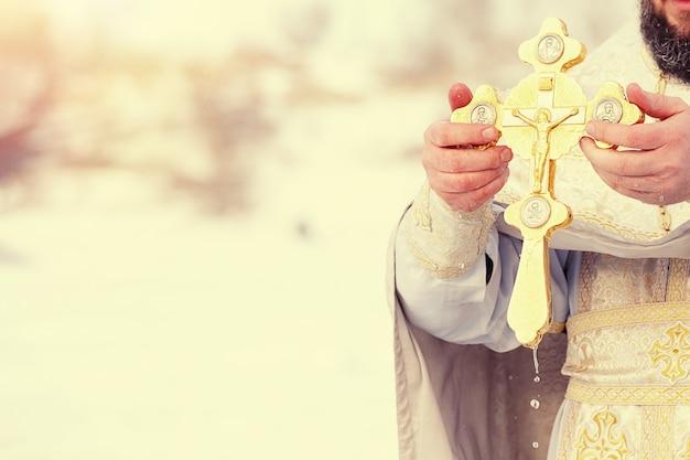 De handen van een priester dopen een orthodox gouden kruis in de rivier. feest van de driekoningen van rusland. afgezwakt beeld.