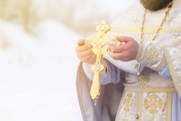 De handen van een priester dopen een orthodox gouden kruis in de rivier. feest van de driekoningen van rusland.