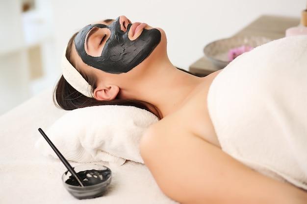 De handen van een schoonheidsspecialist brengen een masker op het gezicht aan met een borstel,