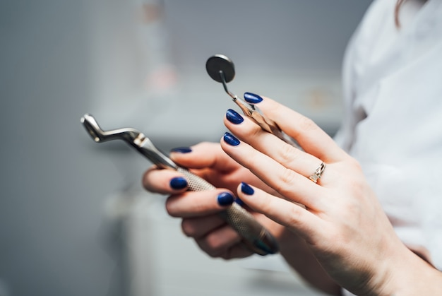 De handen van een stomatoloog met blauwe spijkers houden rainles-instrumenten in kliniek. medische apparatuur in handen van een tandarts