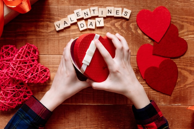 De handen van een tiener openen een valentijnsdag geschenk op een houten achtergrond. harten en vakantiedecor op tafel.