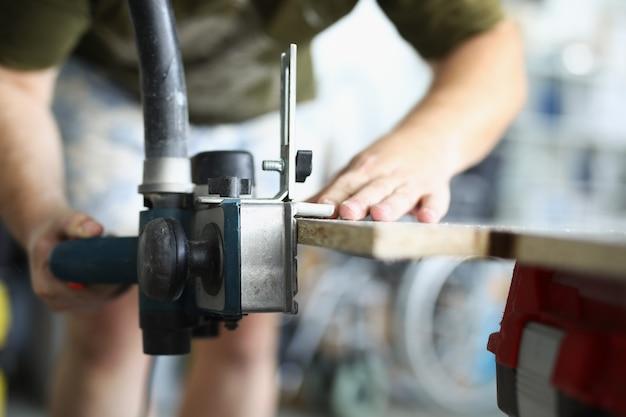 De handen van een timmerman in de werkplaats maken de werkbank vast om met hout te werken