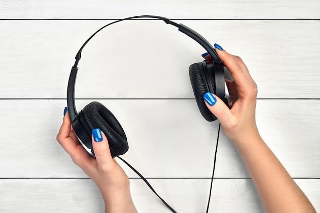 De handen van een vrouw houden zwarte hoofdtelefoons vast