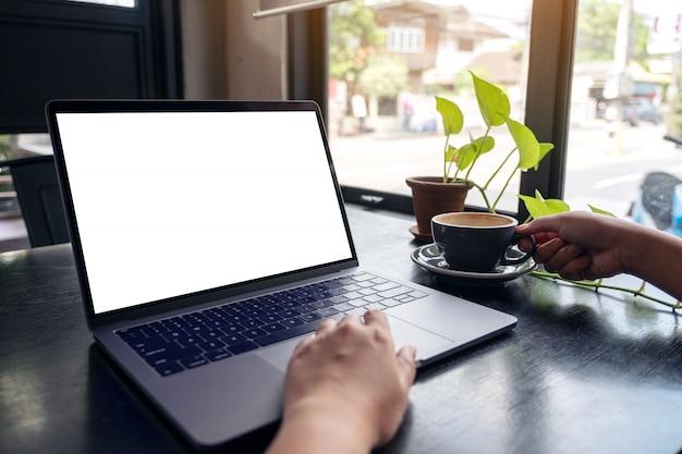 De handen van een vrouw met behulp van laptop met een leeg wit bureaublad terwijl het drinken van warme koffie op houten tafel in café