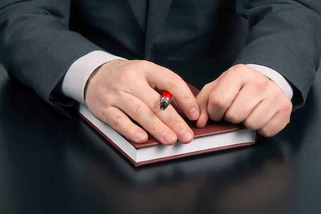 De handen van een zakenman liggen op een notitieblok in het kantoor. succes op het werk