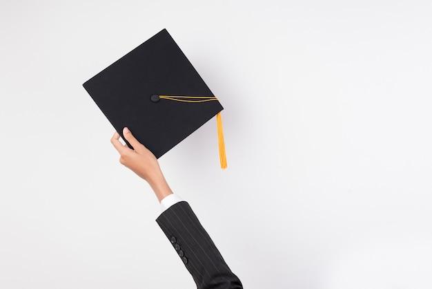 De handen van gediplomeerden die een hoed houden om een hoed op geïsoleerde achtergrond te werpen.