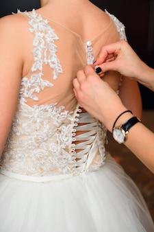 De handen van het bruidsmeisje maken knopen op de rug van de bruid op de trouwjurk vast