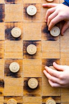 De handen van het kind bewegen stukjes damspel, strijd, strategie en confrontatie.