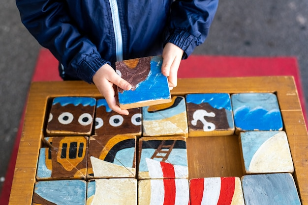 De handen van het kind completeren een ambachtelijke puzzel gemaakt van houten kubussen.