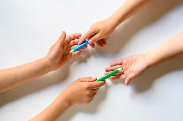 De handen van het kind delen elkaar kleurpotloden op een wit