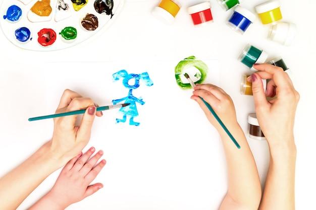 De handen van het kind die een familie schilderen