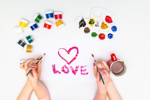 De handen van het kind die een hart schilderen