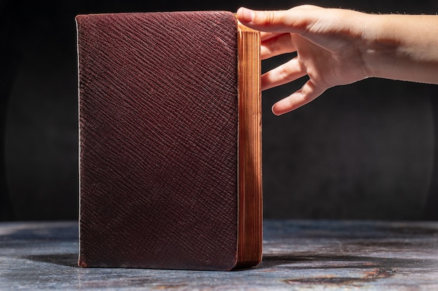 De handen van het kind die zich uitstrekken tot het oude boek. het concept van dorst naar kennis.