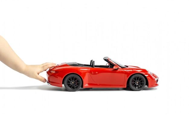 De handen van het kind duwen rode porsche auto