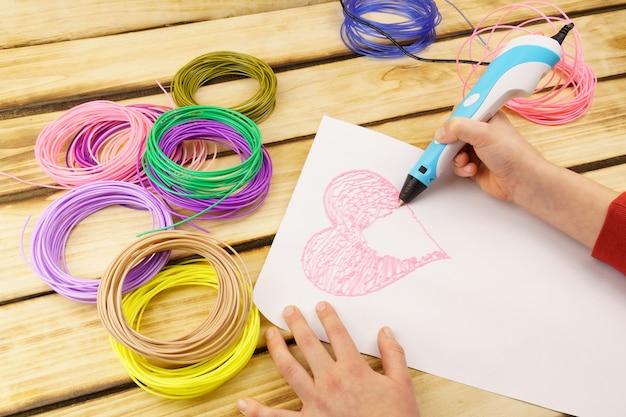 De handen van het kind gebruiken een 3d-printpen om een groot hart te maken.