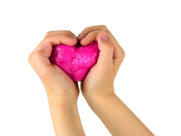 De handen van het kind houden een rood stuk speelgoed vast in de vorm van een hart dat op een wit oppervlak wordt geïsoleerd. antistress voor speelgoed. speelgoed voor de ontwikkeling van handmotoriek.