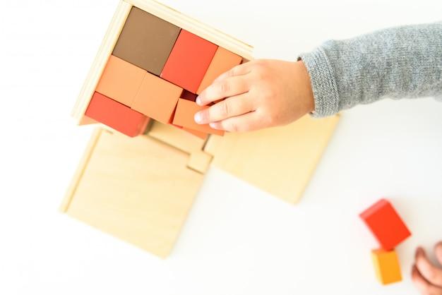 De handen van het kind met behulp van een educatief speelgoed voor hun cognitieve ontwikkeling.