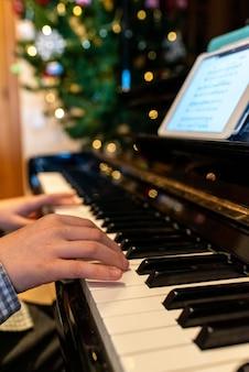 De handen van het kind spelen de sleutels van een piano tijdens kerstmis.