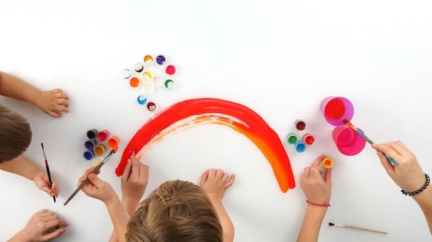 De handen van het kind tekent een regenboog op wit papier