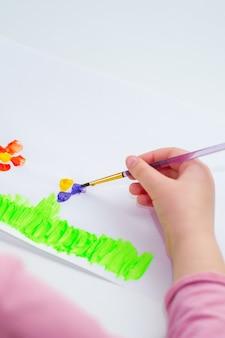 De handen van het kind trekken bloemen op een wit vel papier. kinder en aarde dag concept.